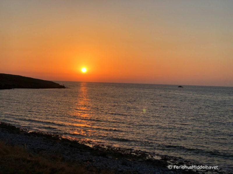 Himmelen er blodrød og gul i det solen går ned ved en odde langs Esentepe kysten, Nord Kypros. Bølger som dovent slår inn mot land.