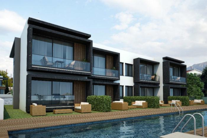 2 etasjes bygninger med balkonger ut mot et basseng.