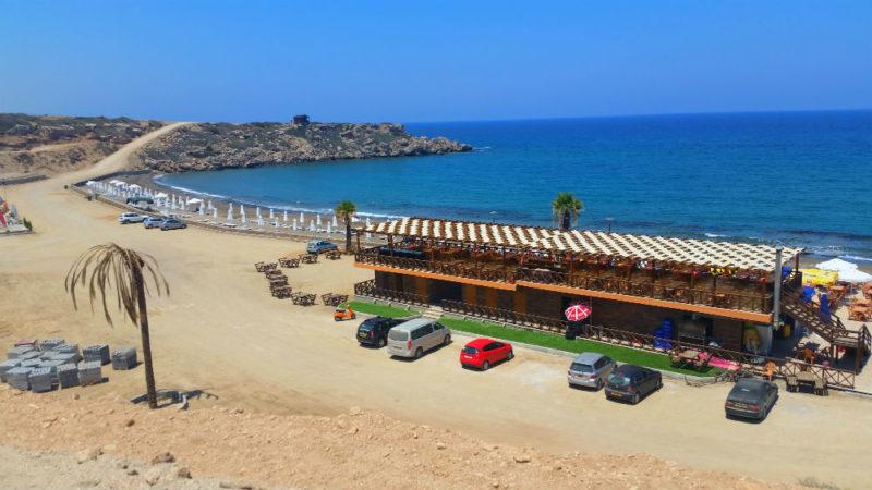 strand ved Middelhavet med en bygning med restaurant, dusj, skifterom og parkerte biler.